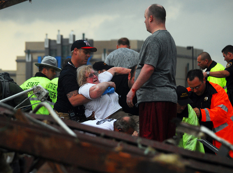 . Emergency workers pull out a woman that was trapped in a building that was destroyed off of 4th Street and Interstate 35 after a tornado ripped through Moore, Okla.,  Monday May 20, 2013.  (AP Photo/ The Transcript,Kyle Phillips )
