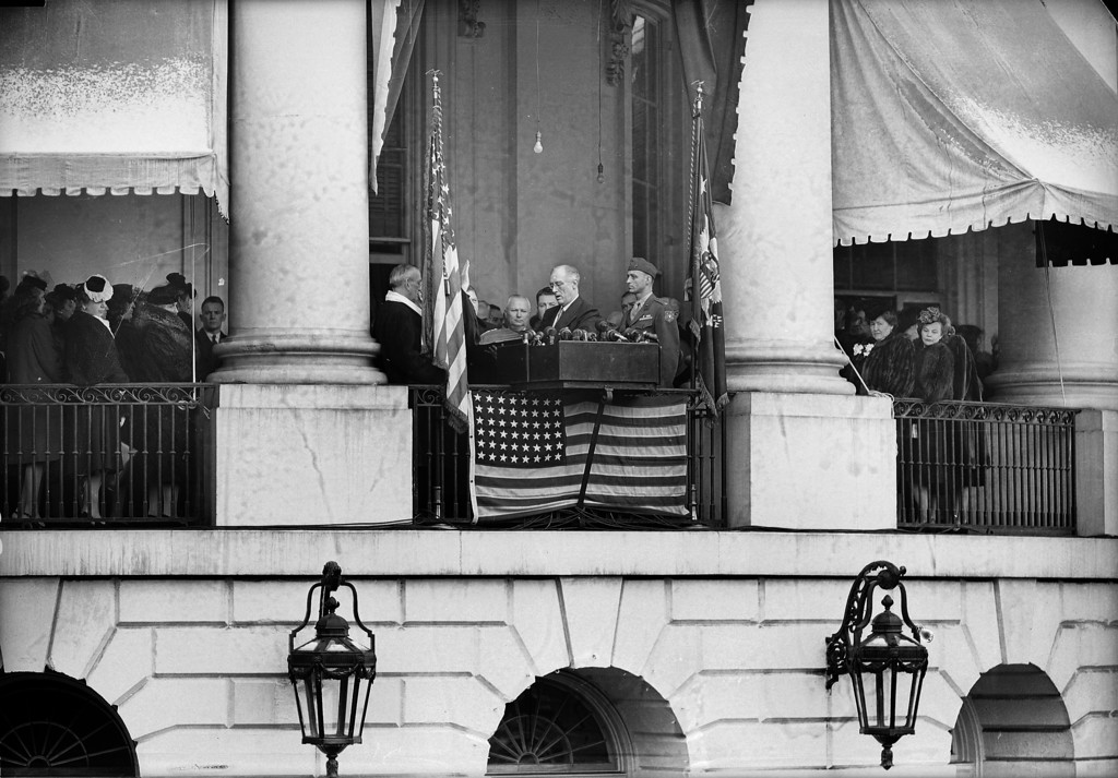 . President Franklin D. Roosevelt , seocnd from right, repeats the oath of office on the rear porch of the White House at noon, Jan. 20, 1945, with Chief Justice Harlan F. Stone (obscured by flag at left) officiating. Others are, from left: Secretary of Senate Edwin Halsey; Charles E. Cropley, clerk of the Supreme Court (face obscured by hand of Chief Justice); Secret Service man Richards; unidentified behind the president, and the president\'s son Col. James Roosevelt. (AP Photo)