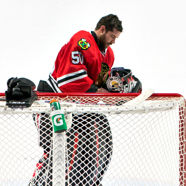 Corey Crawford adjusting his headgear.
