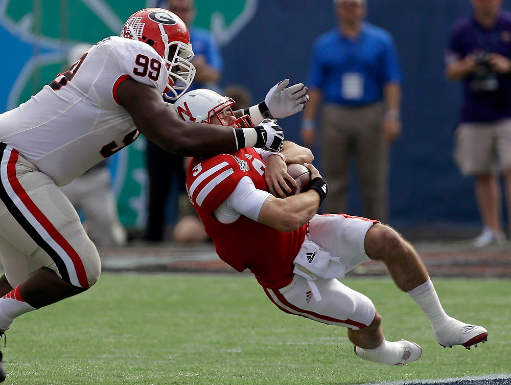 Description of . Georgia defensive lineman Kwame Geathers (99) stops Nebraska quarterback Taylor Martinez (3) for no gain during the first half of the Capital One Bowl NCAA football game, Tuesday, Jan. 1, 2013, in Orlando, Fla. (AP Photo/John Raoux)