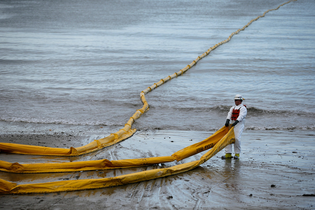 . A worker prepares an oil containment boom at Refugio State Beach, north of Goleta, Calif., Thursday, May 21, 2015. More than 7,700 gallons of oil has been raked, skimmed and vacuumed from a spill that stretched across 9 miles of California coast, just a fraction of the sticky, stinking goo that escaped from a broken pipeline, officials said. (AP Photo/Jae C. Hong)