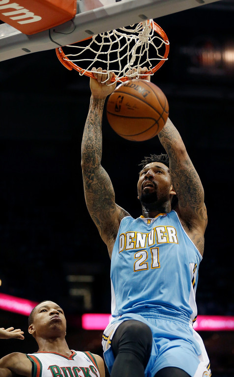 . Denver Nuggets\' Wilson Chandler (21) dunks against Milwaukee Bucks\' Giannis Antetokounmpo, left,  during the first half of an NBA basketball game Thursday, Feb. 20, 2014, in Milwaukee. (AP Photo/Jeffrey Phelps)