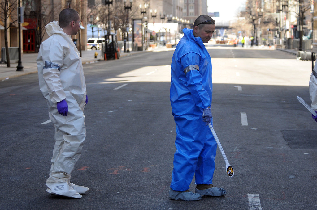 . FBI crime scene investigators look for evidence on Boylston Street after placing an evidence marker  just past Berkeley Street April 17, 2013 in Boston, Massachusetts. Investigators continue to work the scene of two bomb explosions at the finish line of the marathon that killed 3 people and injured over one hundred more. (Photo by Darren McCollester/Getty Images)