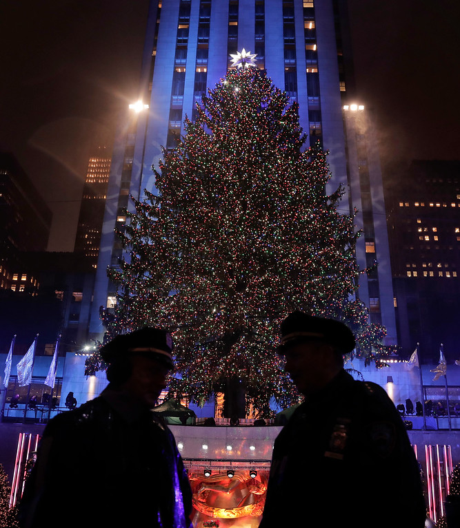 . New York police officers stand across from the Rockefeller Center Christmas tree after the 84th annual Rockefeller Center Christmas tree lighting ceremony, Wednesday, Nov. 30, 2016, in New York. The 94-foot tall Norway spruce is covered with 50,000 multicolored LED lights. (AP Photo/Julie Jacobson)