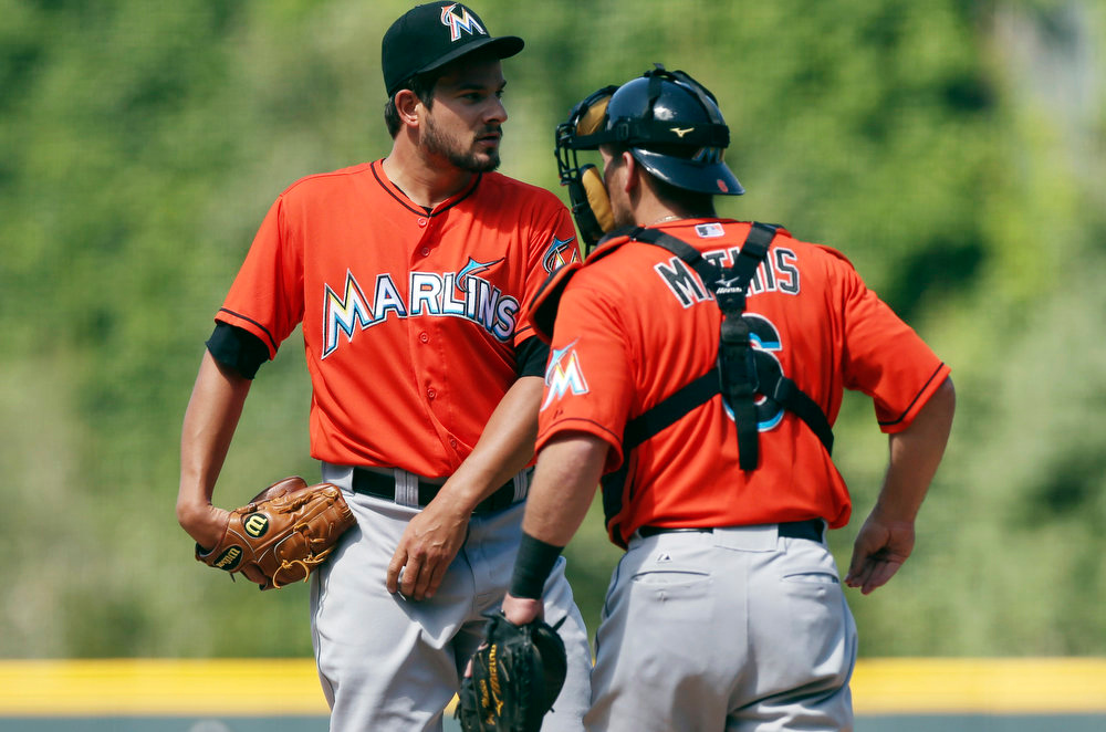 . Miami Marlins catcher Jeff Mathis, right, confers with starting pitcher Brad Hand after he gave up a solo home run to the Colorado Rockies\' Michael McKenry in the first inning of a baseball game in Denver on Sunday, Aug. 24, 2014. (AP Photo/David Zalubowski)