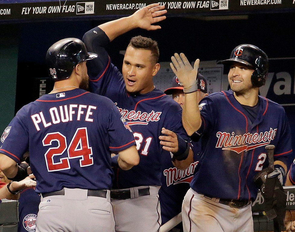 . Minnesota\'s Trevor Plouffe, left, Oswaldo Arcia and Brian Dozier celebrate after Plouffe and Joe Mauer scored on a single by Jordan Schafer during the 10th inning against the Royals. (AP Photo/Charlie Riedel)