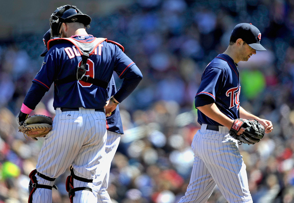 . Twins starter Scott Diamond takes the long walk off the mound after being relieved against the Orioles during the sixth inning. Diamond gave up all six Baltimore runs in Minnesota\'s 6-0 loss to Baltimore. At left is catcher Ryan Doumit.  (Photo by Hannah Foslien/Getty Images)