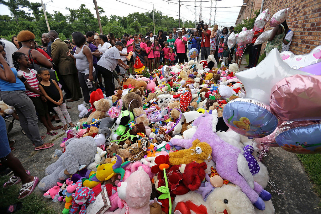 . People place flowers and stuffed animals as they attend a vigil for missing 6-year-old Ahlittia North, at the location where her body was found in a trash bin, just doors down from where she disappeared, in Harvey, La., Tuesday, July 16, 2013. Ahlittia disappeared from her apartment late Friday night or early Saturday morning.  (AP Photo/Gerald Herbert)