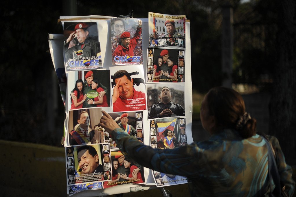 . A woman points at pictures of late Venezuelan President Hugo Chavez in Caracas, on March 8, 2013.   AFP PHOTO/Eitan  ABRAMOVICH/AFP/Getty Images