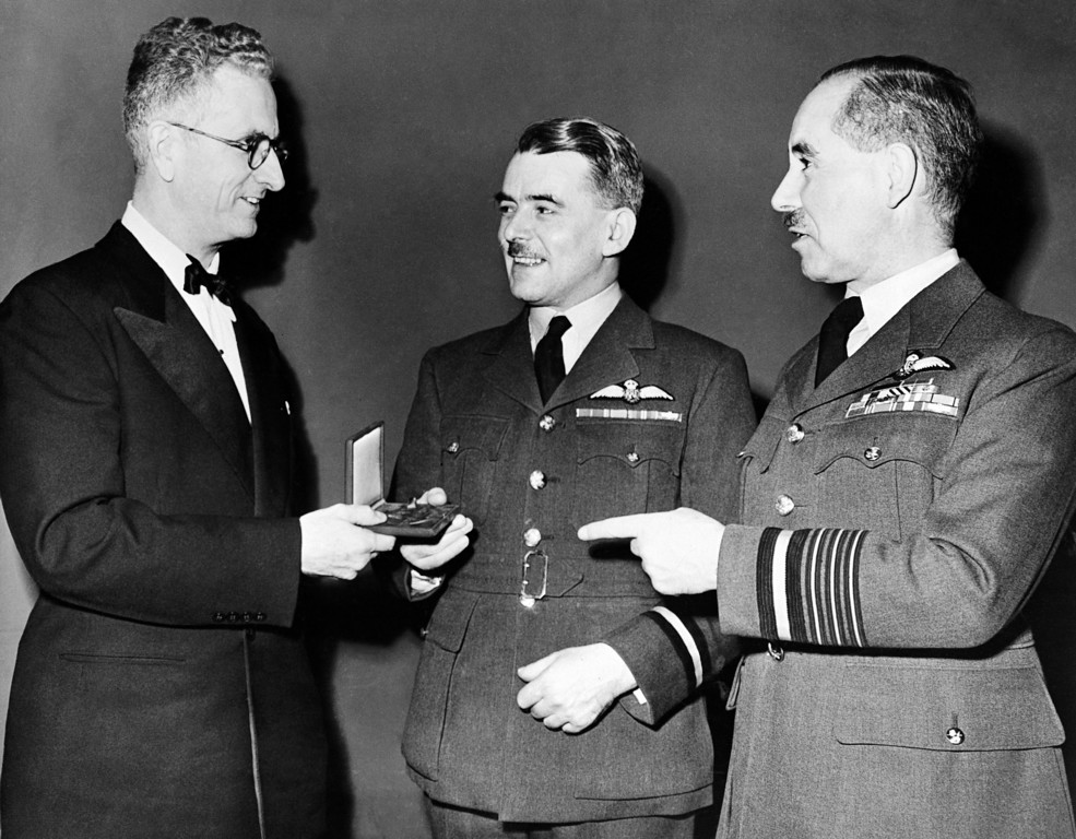 . Air Commodore Frank Whittle, center, of the Royal Air Force, inventor of the turbojet engine, receives the Daniel Guggenheim Medal for Achievement in Aeronautics on Dec. 4, 1946 at the annual meeting of the American Society of Mechanical Engineers in the Hotel Pennsylvania, New York City, U.S.A. Presenting the medal is Theodore P. Wright, Washington, District of Columbia, a former winner of the honor, and at right is Air Chief Marshal Sir Guy Garrod, member of the military staff committee of the United Nations. Commodore Whittle�s home is Coventry, England, and Sir Guy Garrod�s home is in London. (AP Photo)
