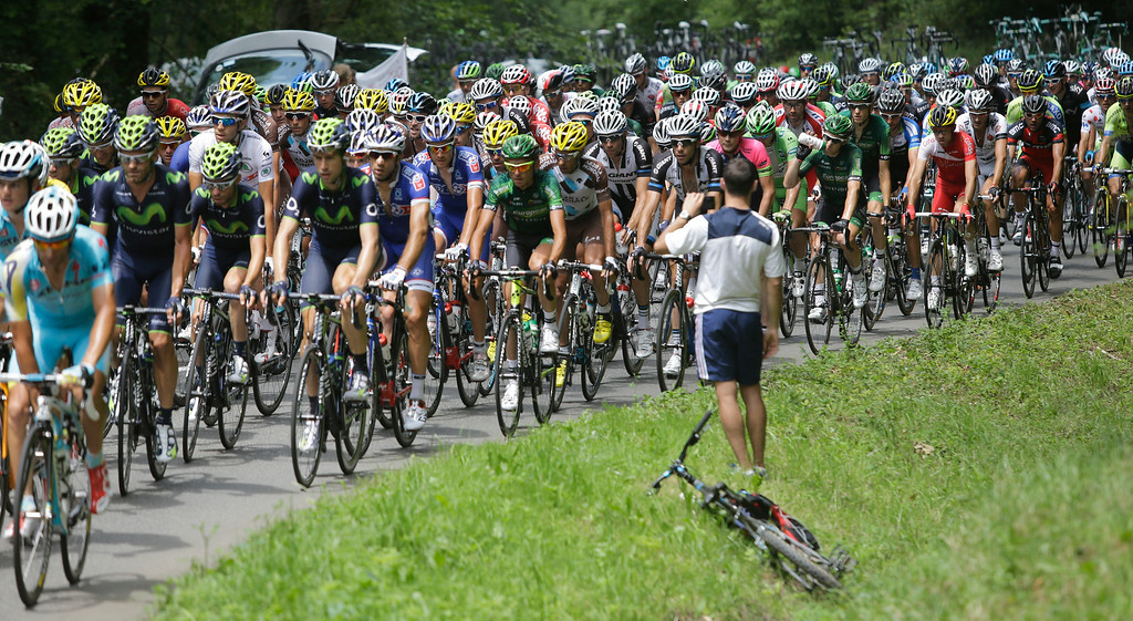 . A spectator films the pack as it passes during the eighteenth stage of the Tour de France cycling race over 145.5 kilometers (90.4 miles) with start in Pau and finish in Hautacam, Pyrenees region, France, Thursday, July 24, 2014. (AP Photo/Laurent Cipriani)