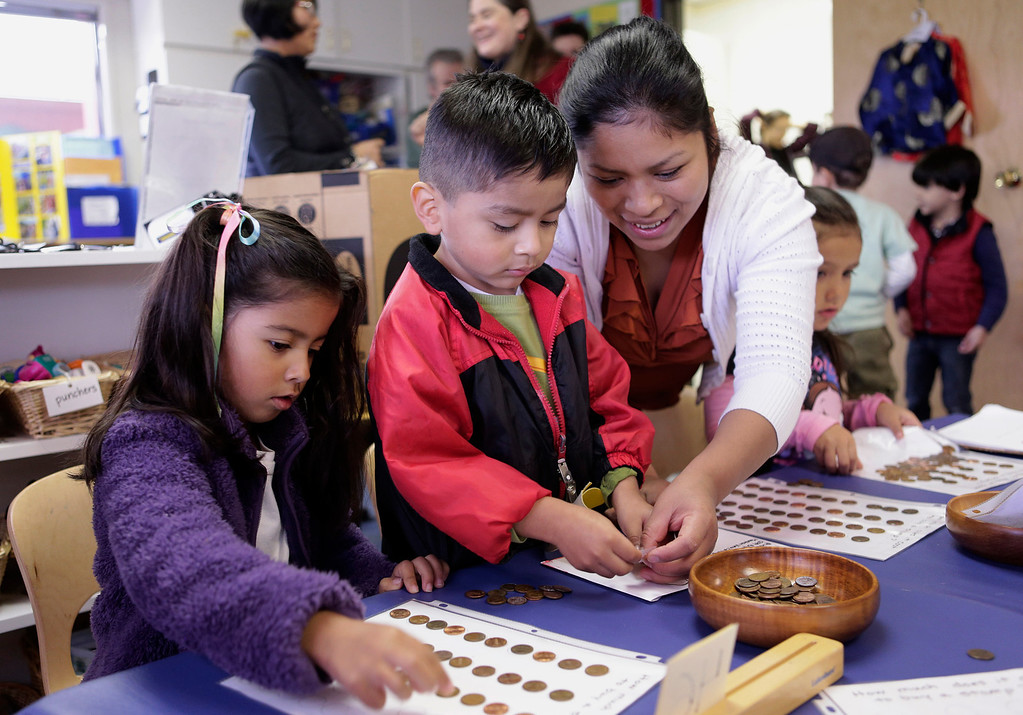 . Maddie Dhillon, 4, Roger Herrera, 4, and parent volunteer, Yaneth Tomas play a money game at the Mountain View Parent Nursery School in Mountain View, Calif. on Friday, Feb. 8, 2013. The Mountain View-Whisman School District has decided that if parents hold back an eligible child from kindergarten, it will help evaluate those children for kindergarten-readiness the following year. Some will be sent to first grade rather than kindergarten. (Gary Reyes/ Staff)