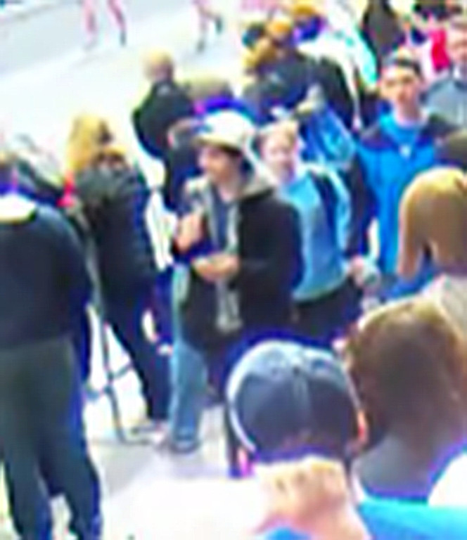 """. This image taken from a video released by the FBI on April 18, 2013 shows a man wearing a white cap walking along the route of the Boston Marathon on April 15. The man and one other are being sought by the FBI in connection with the marathon bombing that killed three. The US Federal Bureau of Investigation (FBI) released the photos and videos of two men sought as suspects in the Boston bombings, urging the public to help identify them. \""""No bit of information... is too small for us to see,\"""" Richard DesLauriers, the agent in charge of the FBI\'s Boston office, told a press conference. /AFP/Getty Images"""