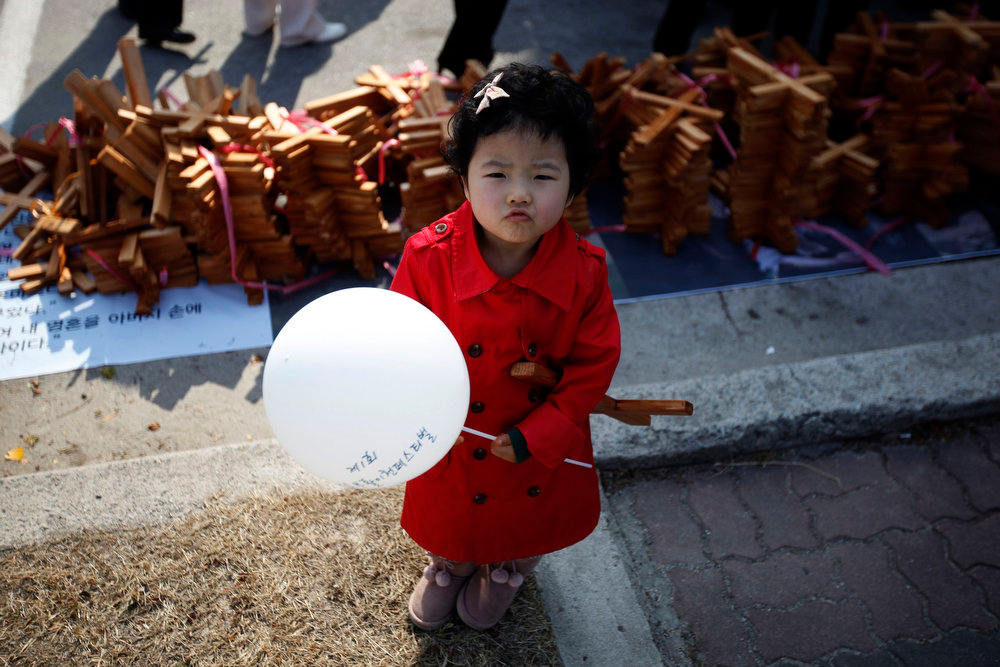 . A girl stands in front of crosses before a procession to celebrate Easter at a church in Icheon, about 80 km (50 miles) southeast of Seoul March 31, 2013. Holy Week is celebrated in many Christian traditions during the week before Easter.  REUTERS/Kim Hong-Ji
