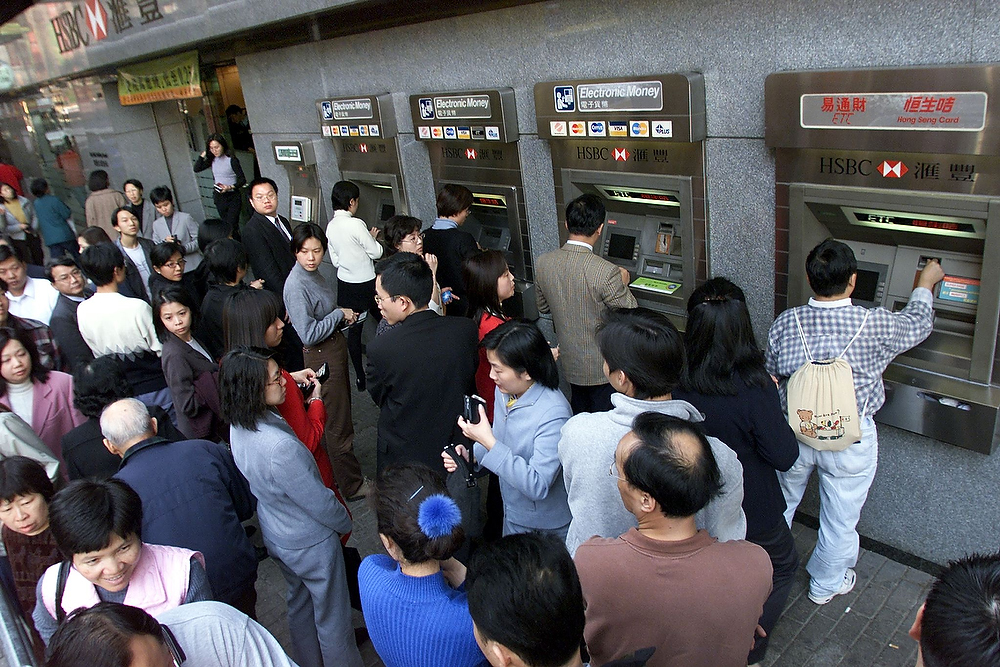 . People line up at a branch of Hong Kong Bank\'s ATM machines to get cash on December 30, 1999 before the millennium rollover.  British banking giant HSBC allayed Asian millennium bug fears on December 30th saying no problems were expected. Due to widespread concerns over computer failures and blackouts when the year changed to 2000, many people feared and prepared for doomsday scenarios. ROBYN BECK/AFP/Getty Images