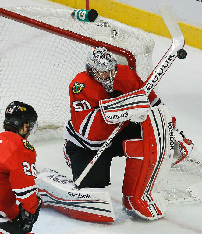 . Chicago Blackhawks goalie Corey Crawford (50) blocks a shot by the Los Angeles Kings during the first period in Game 2 of the NHL hockey Stanley Cup Western Conference finals Sunday, June 2, 2013 in Chicago. (AP Photo/Charles Rex Arbogast)