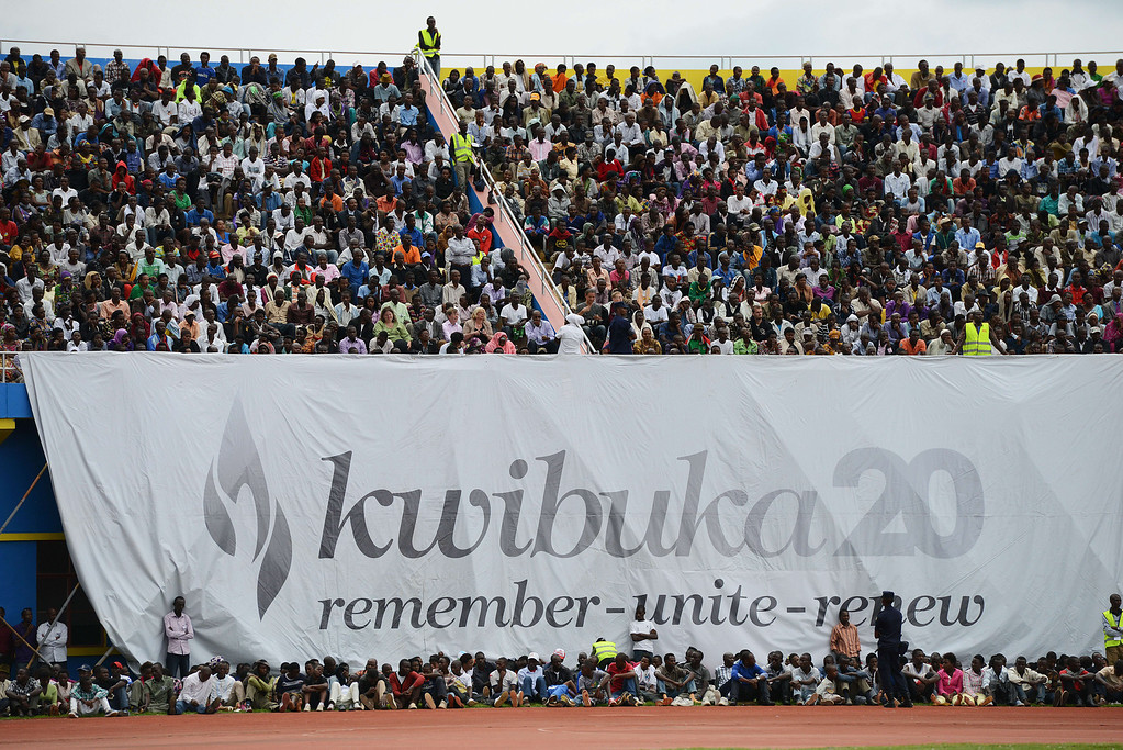 """. Rwandans gather under a banner, with writing in Kinyarwanda reading \""""Remember 20\"""", at the Amahoro stadium in Kigali on April 7,2014, during a ceremony marking the 20th anniversary of Rwanda\'s genocide. Rwanda on April 7 held solemn commemorations marking the 20th anniversary of the genocide, with many survivors overcome with grief as they relived the trauma of the massacres that left nearly a million dead. The events also bore reminders of festering anger, as a major diplomatic row broke out over renewed allegations of French complicity in the genocide.  AFP PHOTO / SIMON MAINA/AFP/Getty Images"""