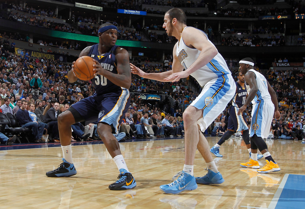 . Memphis Grizzlies forward Zach Randolph, left, pulls in a loose ball as Denver Nuggets forward Kosta Koufos covers in the first quarter of an NBA basketball game in Denver, Friday, March 15, 2013. (AP Photo/David Zalubowski)