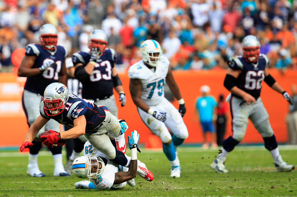 . Julian Edelman #11 of the New England Patriots is tackled by  Nolan Carroll #28 of the Miami Dolphins at Sun Life Stadium on December 15, 2013 in Miami Gardens, Florida.  (Photo by Chris Trotman/Getty Images)