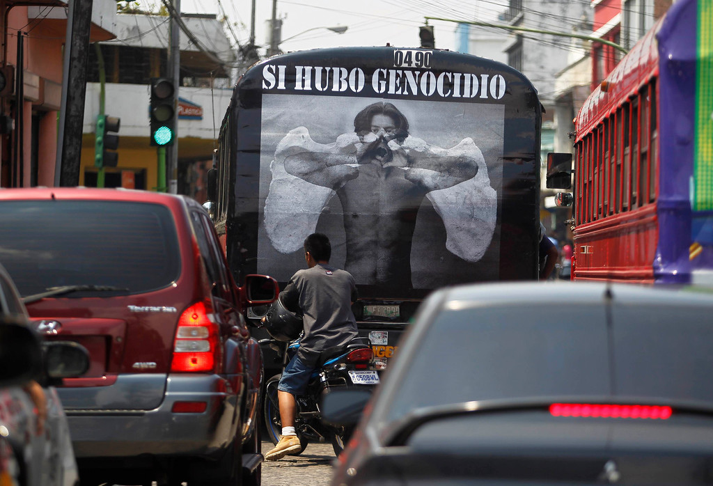 """. A man rides pass a poster on the back of bus at the streets of Guatemala City, May 8, 2013. During the internal armed conflict in Guatemala, between 1960 and 1996 around 200,000 people were forcibly disappeared or killed and that 669 massacres had taken place, mainly in Indigenous villages. The poster reads, \""""Justice for Genocide\"""". REUTERS/Jorge Dan Lopez"""