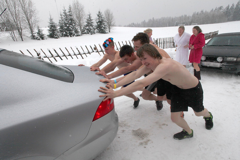 . People push a car during the European Sauna Marathon in Otepaa February 10, 2013. More than 600 participants took part in the event by visiting 20 saunas with a total distance of over 100 km (62 miles). Picture taken February 10, 2013.  REUTERS/Ints Kalnins (ESTONIA - Tags: SOCIETY)