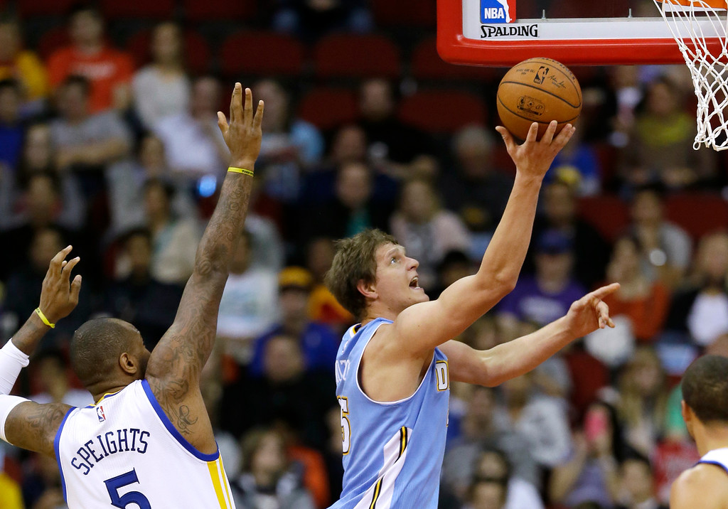 . Denver Nuggets center Timofey Mozgov, right, drives to the basket past Golden State Warriors forward Marreese Speights during the first half of a preseason NBA basketball game, Thursday, Oct. 16, 2014, in Des Moines, Iowa. (AP Photo/Charlie Neibergall)