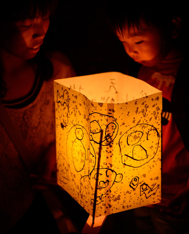 . A mother and her son look at their paper lantern lit in remembrance for victims of the 1945 atomic bombing of Hiroshima before floating it on the Motoyasu River in front of the Atomic Bomb Dome at the Peace Memorial Park in Hiroshima, western Japan, on August 6, 2013. Tens of thousands gathered at the park in Hiroshima on August 6 to mark the 68th anniversary of the US atomic bombing of the city, as anti-nuclear sentiment runs high in the country. AFP PHOTO / TORU  YAMANAKA/AFP/Getty Images