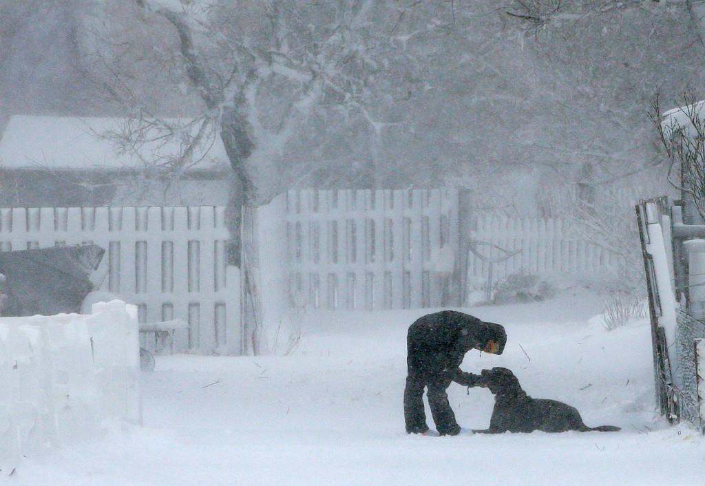 . Whitney Eakin, of Scituate, Mass., plays with her Labrador mix dog named Rudder, during a winter storm, Tuesday, March 13, 2018, in Scituate. The nor\'easter is expected to deliver up to 2 feet of snow to some areas of New England. (AP Photo/Steven Senne)