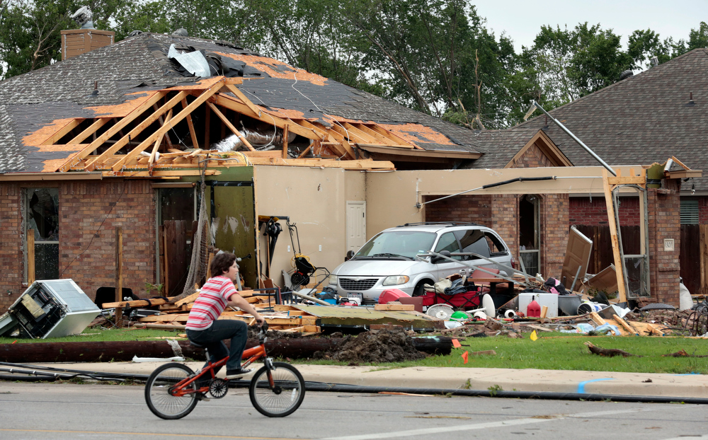 . A child rides his bike past damaged homes on Thursday, May 16, 2013, after a tornado destroyed part of Cleburne, Texas late Wednesday night.  A rash of tornadoes slammed into several small communities in North Texas overnight, leaving at least six people dead, dozens more injured and hundreds homeless. The violent spring storm scattered bodies, flattened homes and threw trailers onto cars.  (AP Photo/The Dallas Morning News, Michael Ainsworth)