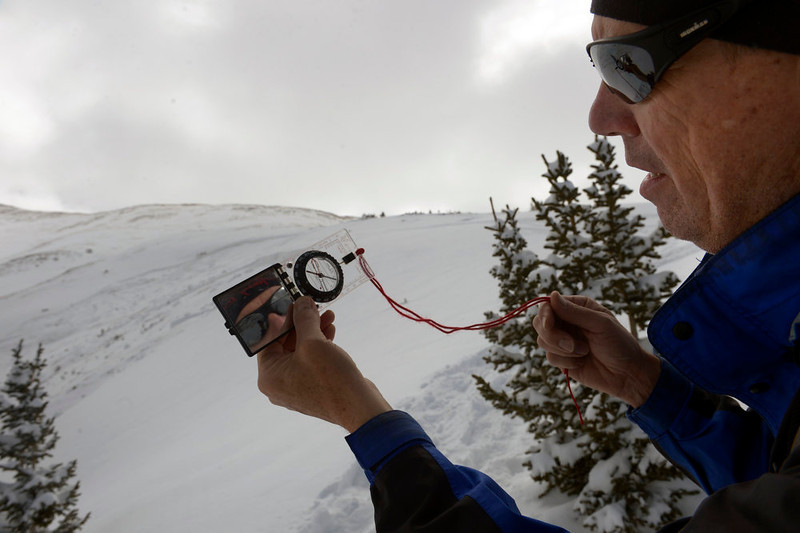 . Back country skier TJ Carroll looks at the slope degree on his compass of the avalanche site.  Members of the Colorado Avalanche Information Center were on site to  carefully deconstruct the area of a deadly avalanche on Sheep Creek off of Loveland Pass on Sunday April 21, 2013.  The avalanche was on the western flank of Mount Sniktau and happened around 2:00 pm on Saturday.  (Photo By Helen H. Richardson/ The Denver Post)
