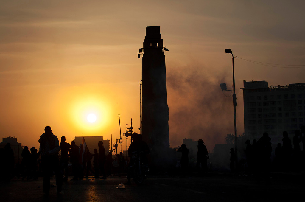 . The sun sets during clashes between Egyptian protesters and riot police in downtown Cairo, Egypt, Saturday, March 9, 2013.  (AP Photo/Nasser Nasser)