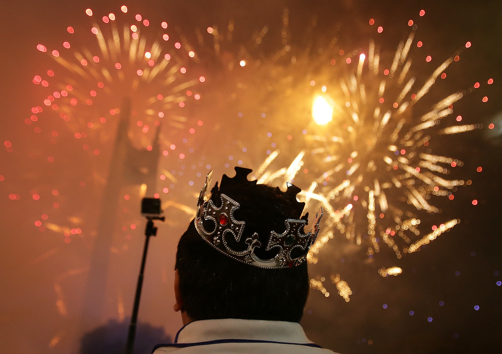 . A Filipino watches a fireworks display at the Quezon Memorial Circle in suburban Quezon city, north of Manila, Philippines on Thursday, Jan. 1, 2015. (AP Photo/Aaron Favila)
