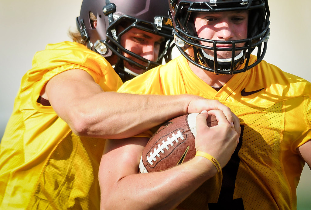 . Gophers quarterback Mitch Leidner, right, tries to keep hold of the ball as quarterback Philip Nelson reaches in during the team\'s first fall camp practice in Minneapolis on Friday, Aug. 2, 2013. (Pioneer Press: Ben Garvin)