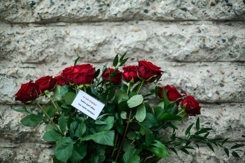 . Flowers with the message reading \' I am Charlie,  All is allowed for satire, except dying \'    are  placed  in front of the French Embassy in Berlin, Thursday, Jan. 8, 2015 to commemorate the victims killed in an attack at the Paris offices of the weekly newspaper Charlie Hebdo,.  Masked gunmen stormed the Paris offices of a weekly newspaper that caricatured the Prophet Muhammad, methodically killing 12 people Wednesday, including the editor, before escaping in a car. It was France\'s deadliest postwar terrorist attack. (AP Photo/Markus Schreiber)