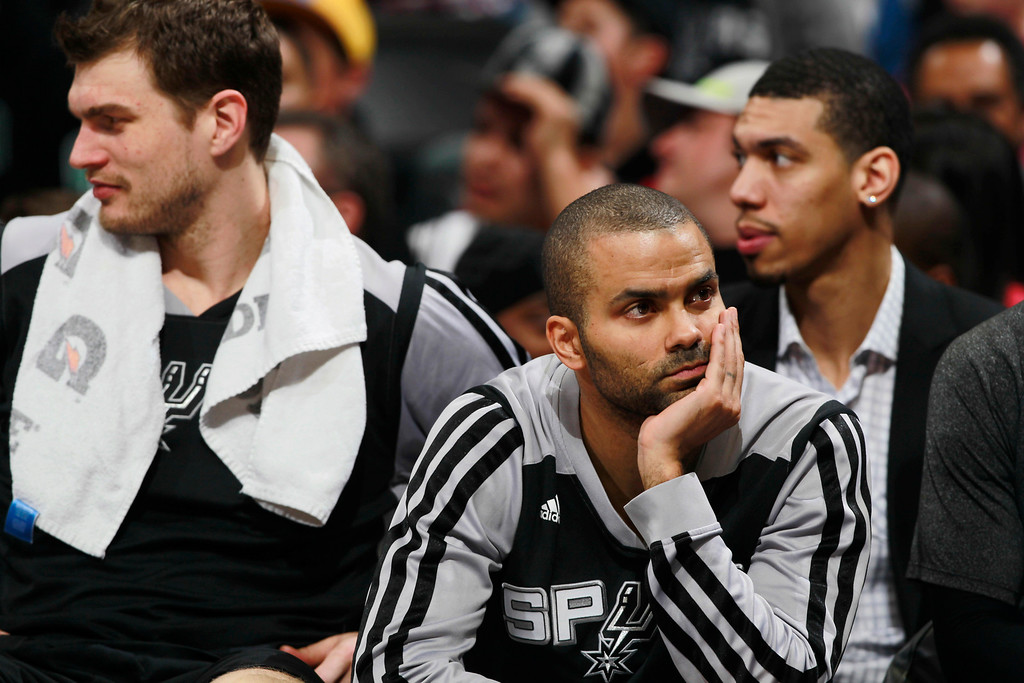 . San Antonio Spurs guard Tony Parker, right, watches fro bench along with forward Tiago Splitter,  left, of Brazil as the Spurs build a 30-point lead against the Denver Nuggets in the fourth quarter of the Spurs\' 133-102 victory in an NBA basketball game in Denver on Friday, March 28, 2014. (AP Photo/David Zalubowski)