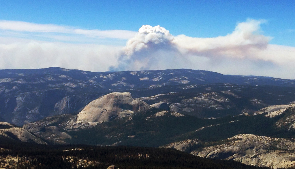 . Smoke clouds from the Rim Fire in the western Sierra Nevada loom up some 20 miles behind the famed granite monolith known as Half Dome, left center, in Yosemite Valley in Yosemite National Park, Calif., Saturday, Aug. 24, 2013. (AP Photo/Tami Abdollah)