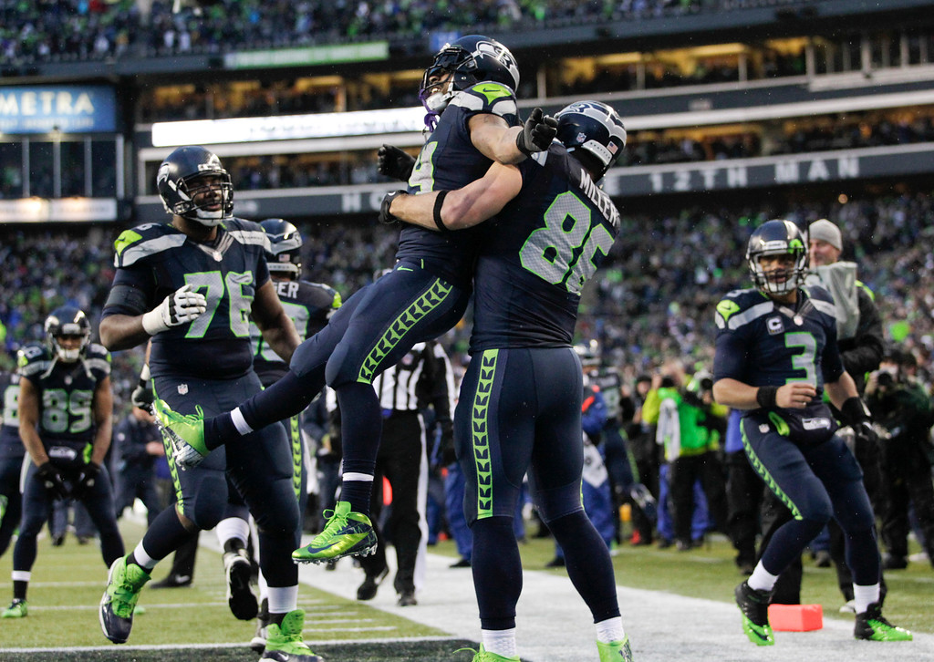 . Seattle Seahawks running back Marshawn Lynch (24) celebrates with tight end Zach Miller (86) after running for a 31-yard touchdown against the New Orleans Saints during the fourth quarter of an NFC divisional playoff NFL football game in Seattle, Saturday, Jan. 11, 2014. (AP Photo/John Froschauer)