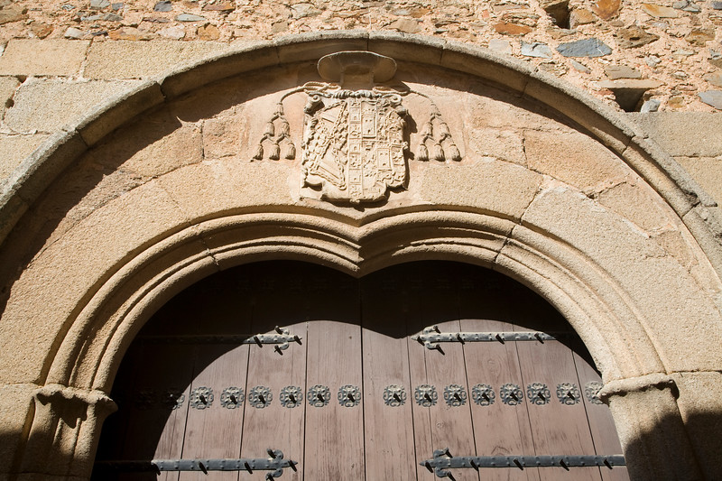 Stone coat of arms of the Bishop over a doorway, Caceres, Spain