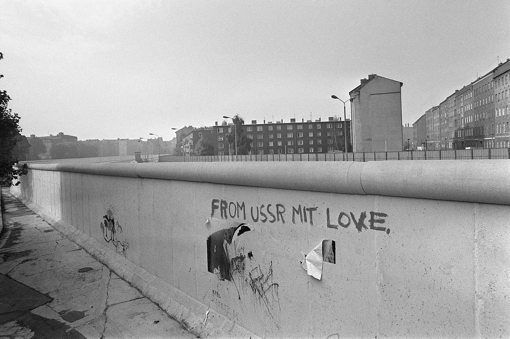 """. Picture taken on October 13, 1976 of an inscription \""""from USSR mit love\"""" on the Berlin Wall. The Berlin wall built by the East German government to seal off East Berlin from the part of the city occupied by the three main western powers (USA, Great Britain and France), and to prevent mass illegal emigration to the West. The wall, built along the border between German Democratic Republic (GDR) and Federal Republic of Germany, was the scene of the shooting of many East Germans who tried to escape from GDR. The two countries remained divided until November 1989 when the wall was unexpectedly opened following increased pressure for political reform in GDR.        (Photo credit RALPH GATTI/AFP/Getty Images)"""