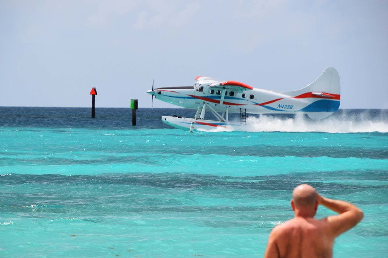 A seaplane lands in the Gulf of Mexico's aqua-colored water.