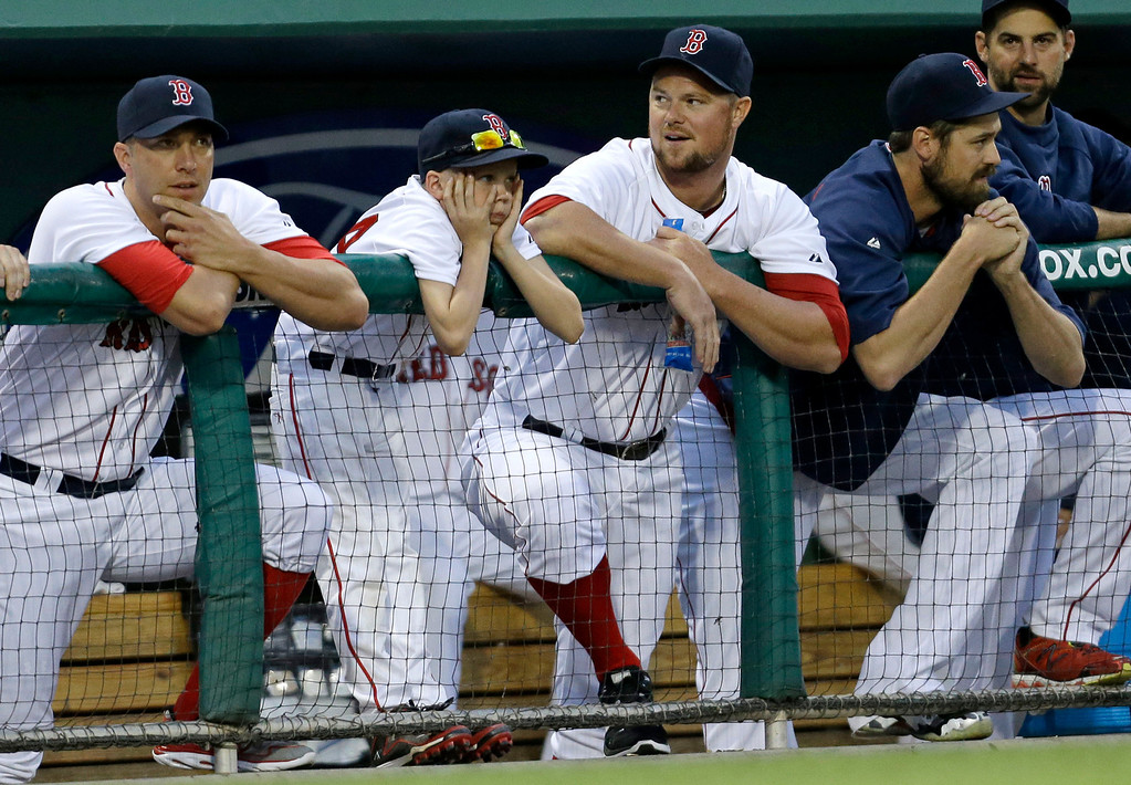 . Boston Red Sox starting pitcher Jon Lester, second right, watches from the dugout in the second inning of an exhibition baseball game against the Minnesota Twins.  (AP Photo/Gerald Herbert)