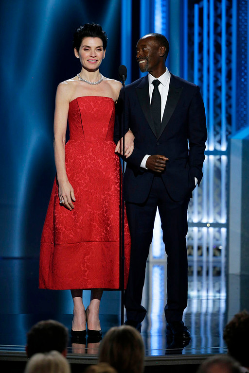 . In this image released by NBC, presenters Julianna Margulies, left, and Don Cheadle speak at the 72nd Annual Golden Globe Awards on Sunday, Jan. 11, 2015, at the Beverly Hilton Hotel in Beverly Hills, Calif. (AP Photo/NBC, Paul Drinkwater)