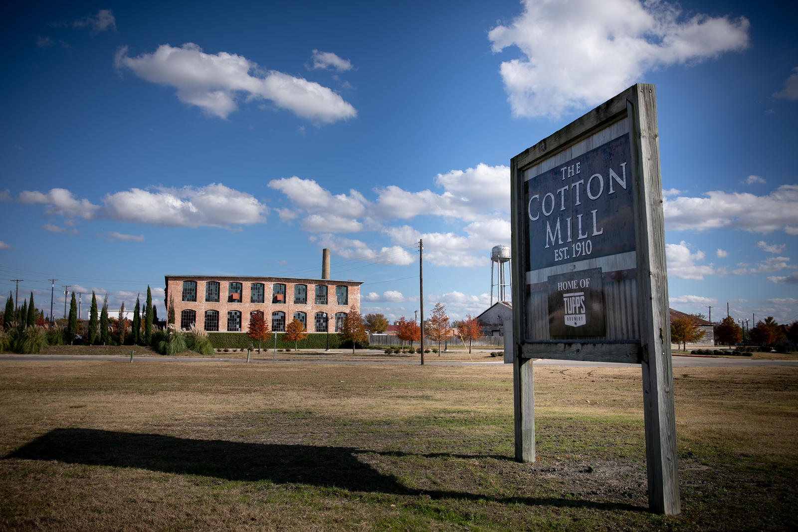 sign that reads the cotton mill est. 1910 with the venue in the background
