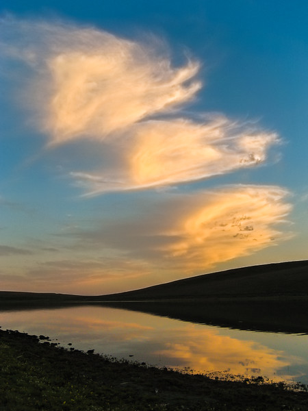 Beautiful clouds form over a small lake