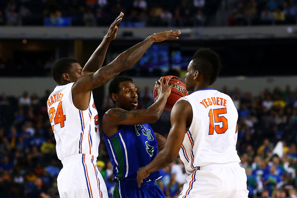 . ARLINGTON, TX - MARCH 29:  Bernard Thompson #2 of the Florida Gulf Coast Eagles is guarded by Casey Prather #24 and Will Yeguete #15 of the Florida Gators in the first half during the South Regional Semifinal round of the 2013 NCAA Men\'s Basketball Tournament at Dallas Cowboys Stadium on March 29, 2013 in Arlington, Texas.  (Photo by Ronald Martinez/Getty Images)