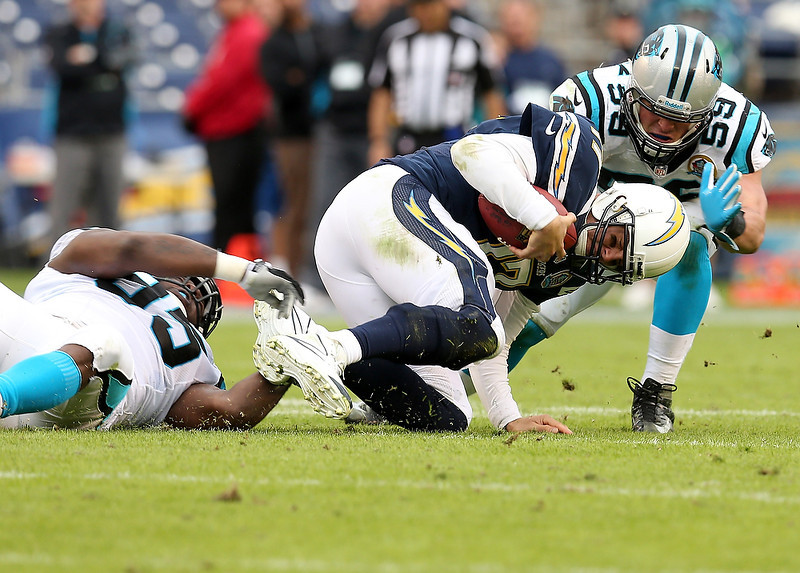 . Quarterback Philip Rivers #17 of the San Diego Chargers is tackled by defensive end Charles Johnson #95 and linebacker Luke Kuechly #59 of the Carolina Panthers at Qualcomm Stadium on December 16, 2012 in San Diego, California. The Panthers won 31-7.  (Photo by Stephen Dunn/Getty Images)