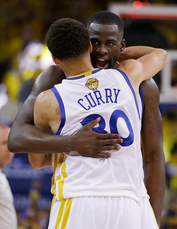 . Golden State Warriors guard Stephen Curry (30) hugs forward Draymond Green after the overtime period of Game 1 of basketball\'s NBA Finals in Oakland, Calif., Thursday, June 4, 2015. The Warriors won 108-100. (AP Photo/Ben Margot)