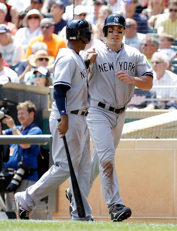 . New York\'s Zoilo Almonte, left, and Travis Hafner score on a two-run double by Vernon Wells in the first inning. (AP Photo/Jim Mone)