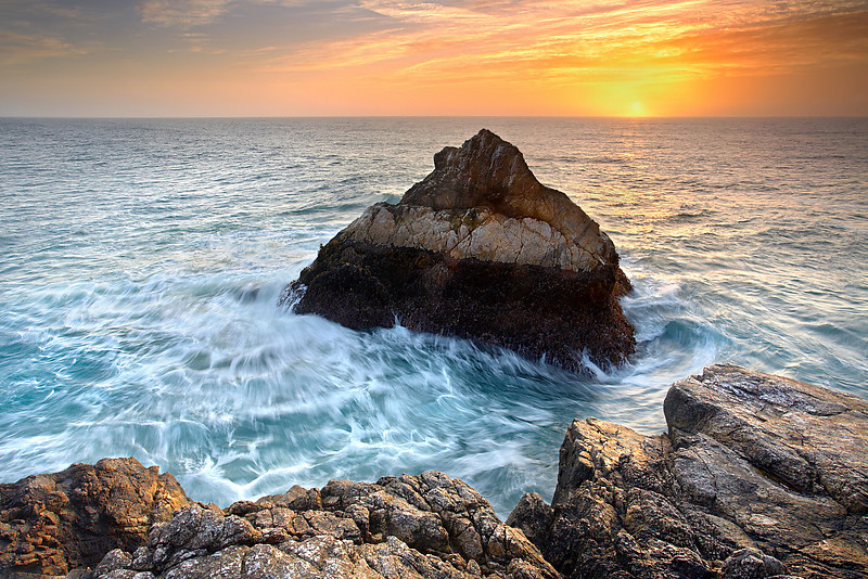 I have always liked to visit McClure's Beach to see the dramatic wave action. But it is usually too violent to get a good shot of it.  On this evening however, low tide and a partly cloudy sunset allowed me to capture the light on the rock and water without getting drenched.   The warm tone of the light showed off every detail and color in the storm-beaten rock at it's best.  Once I had a good view of the rock, I waited for the best light and then timed the wave to show how the water moved around the rock.