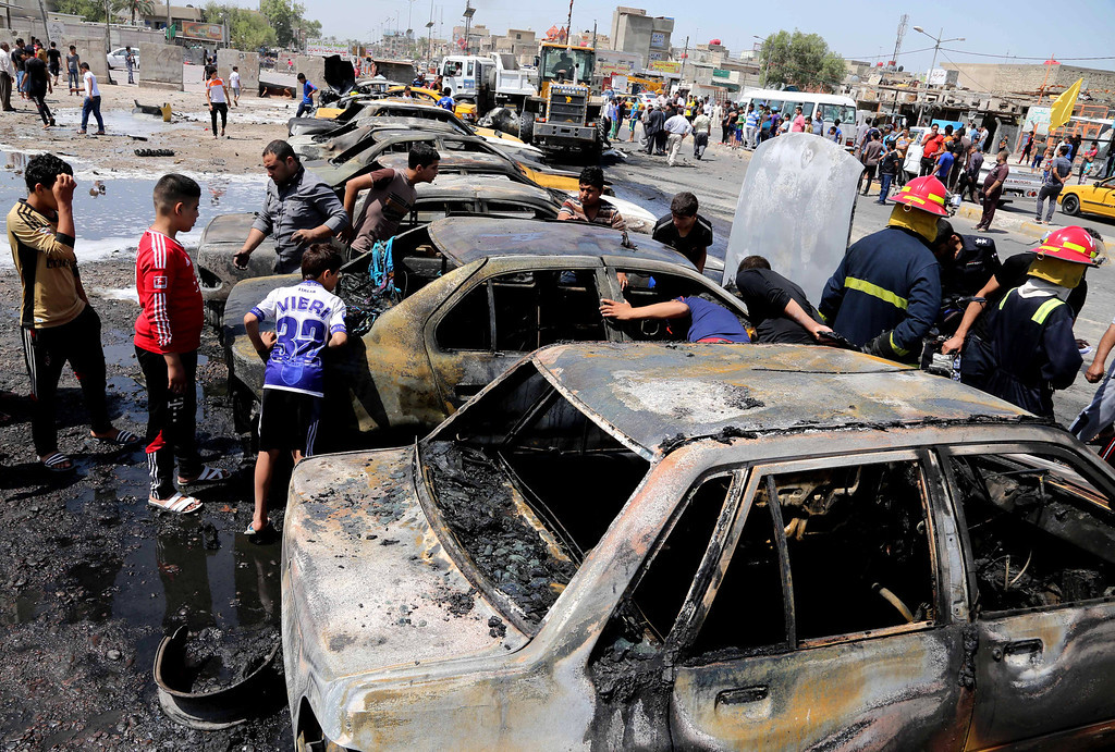 . Civilians inspect the site of a car bomb explosion in the Shiite stronghold of Sadr City, in Baghdad, Iraq, Tuesday, May 13, 2014.  (AP Photo/Karim Kadim)